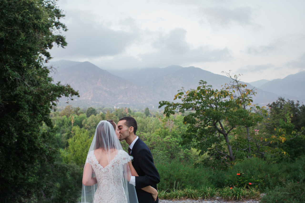 A wedding couple share a kiss in the forest.
