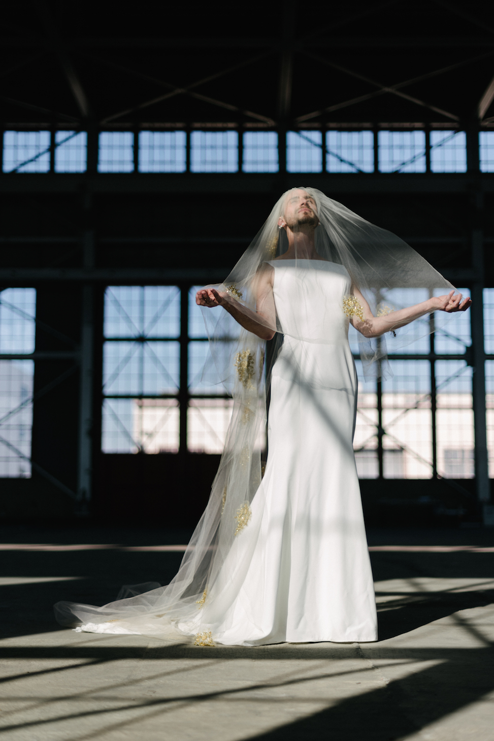 A man stands in a warehouse wearing a veil and Maggie Sottero dress style 'Alice.'