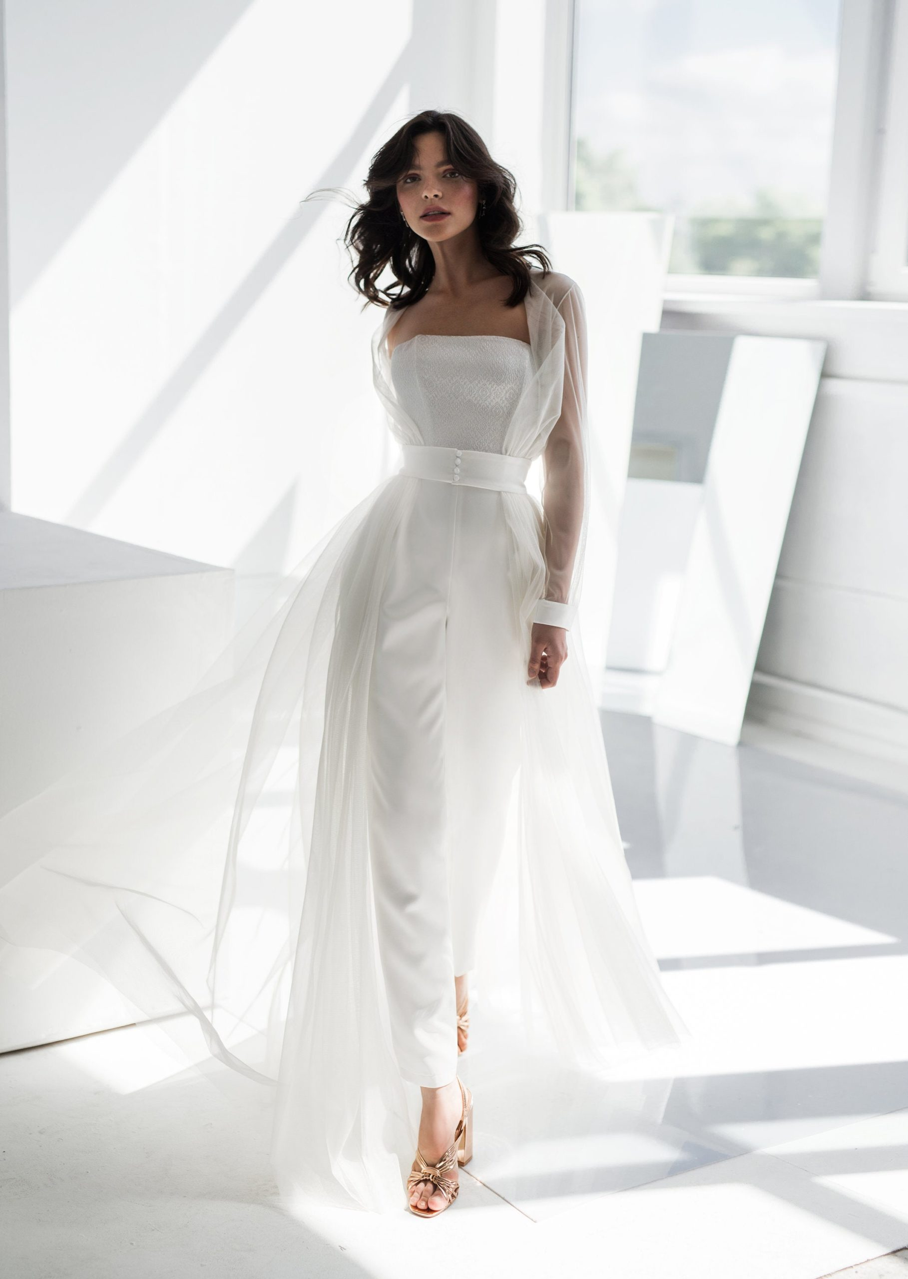 A woman wears a flowy wedding jumpsuit.