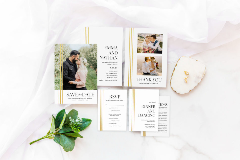 Flat lay of the complete Modern Wedding Suite from the Martha Stewart for Mixbook Collection featuring rings, an invitation, rsvp card, thank you card and more.