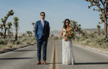 Groom in a blue suit and bride in a lace dress stand in the middle of a deserted highway in Joshua Tree