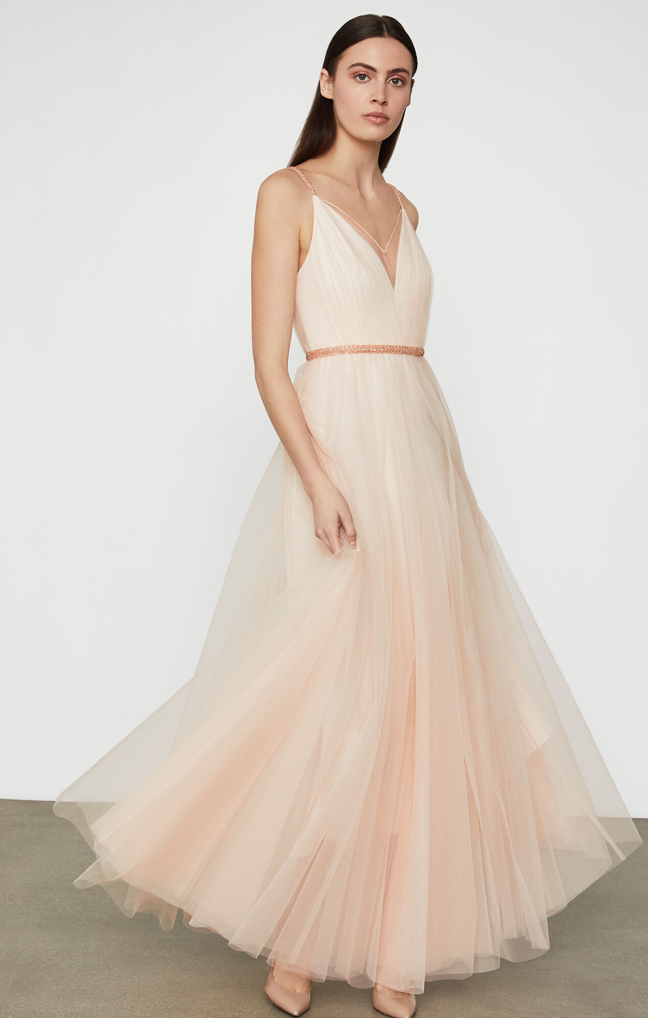 Woman with dark hair in blush colored flowy ballerina style floor length gown