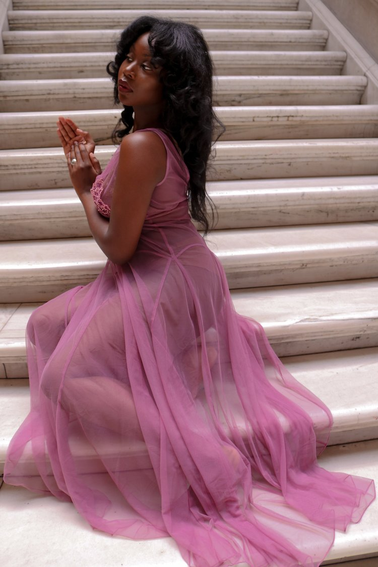 black womxn wearing a transparent nightgown sitting on the stairs