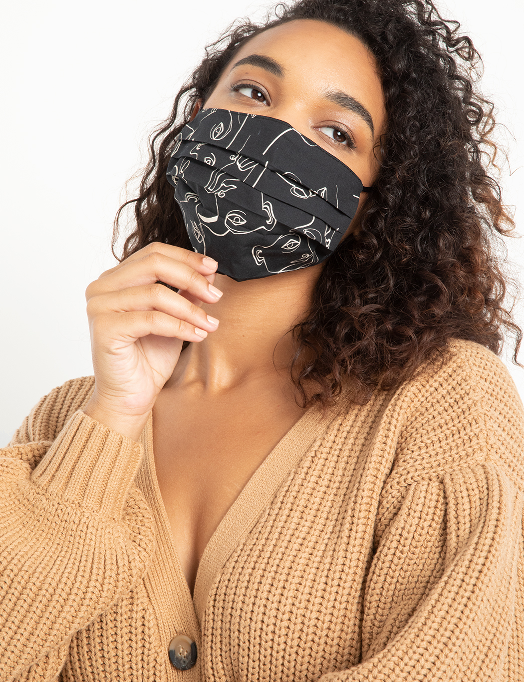 a woman with dark curly hair wearing a face printed face mask