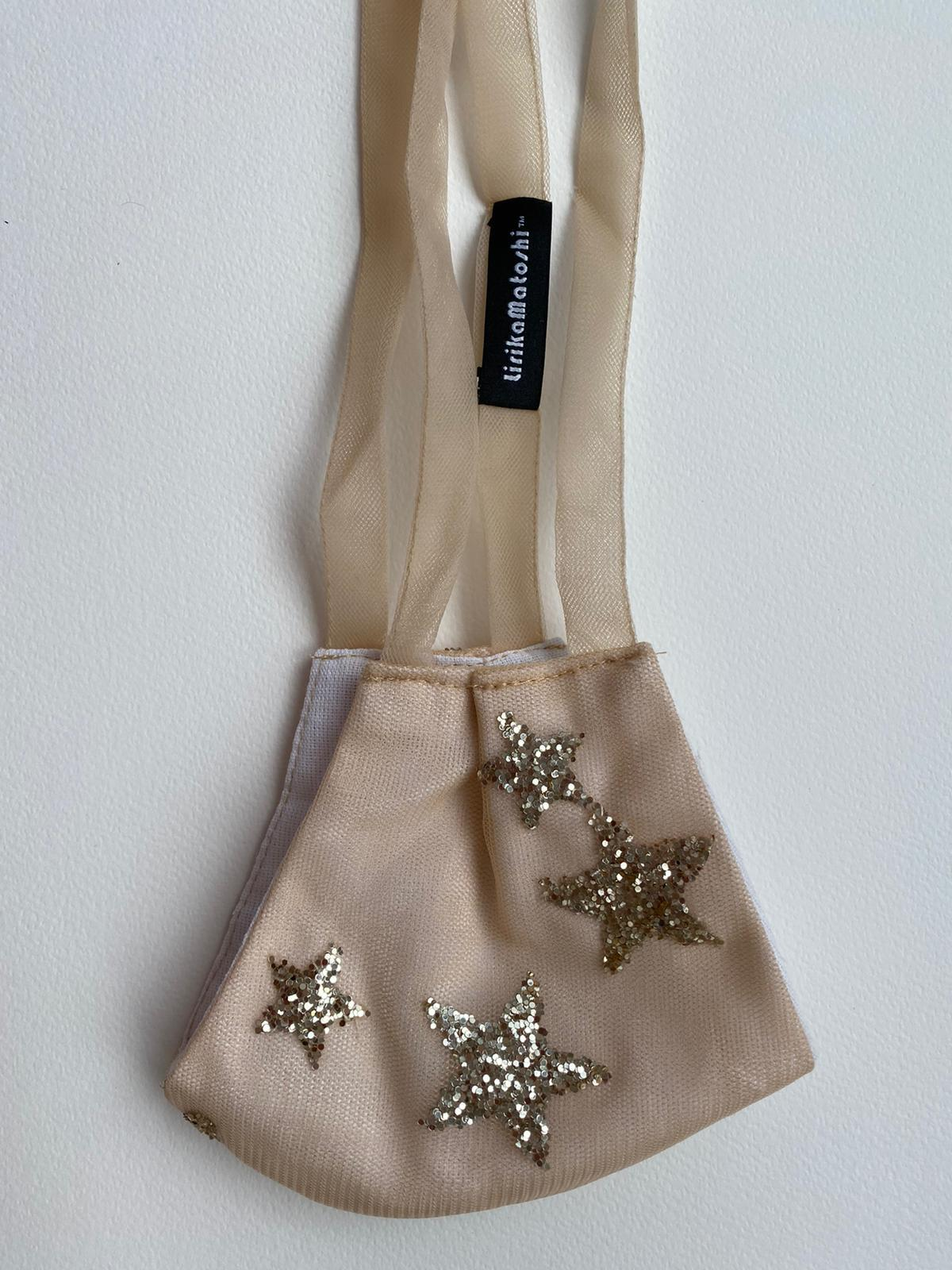 tan mask with glitter star patches