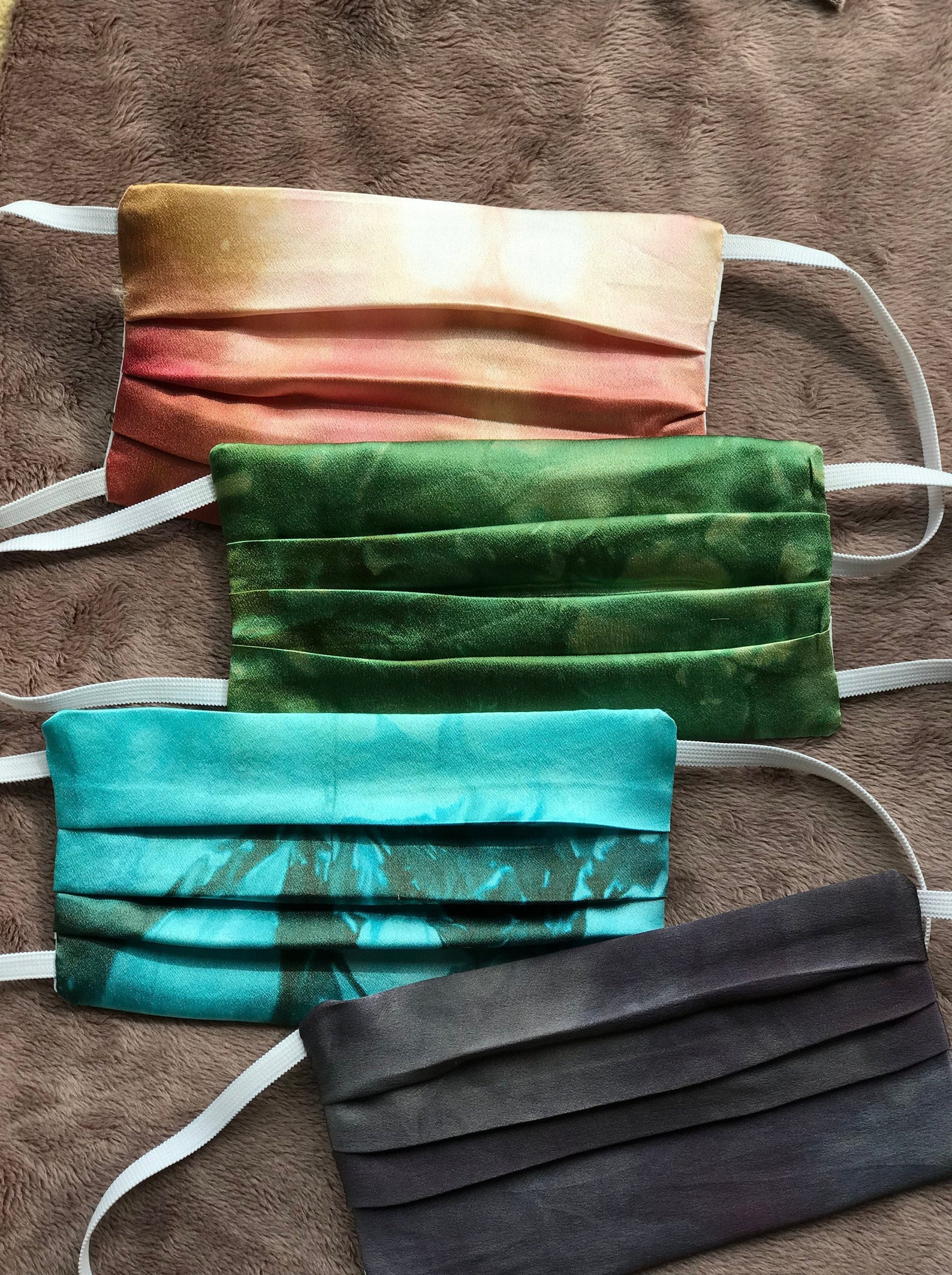 A set of 4 reusable silk face masks. Color options are orange, green, blue and black