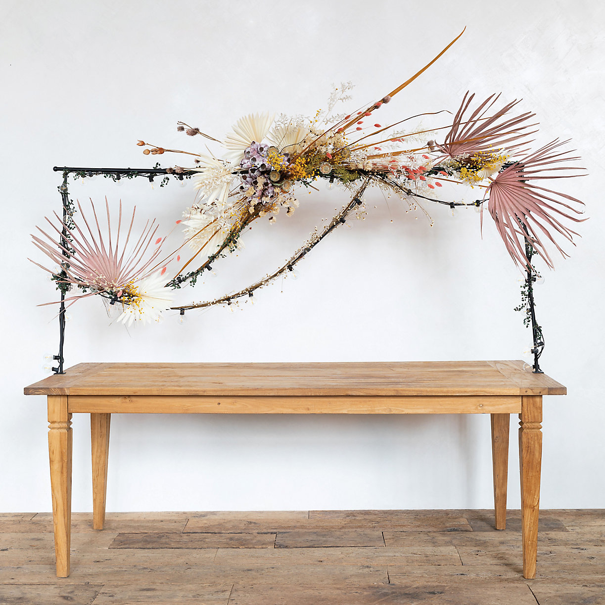 pink palm leaves and other dried flowers attached to a rod over a dinner table