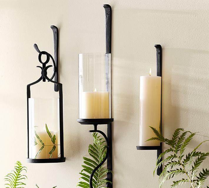 cast iron black wall hangings holding white pillar candles