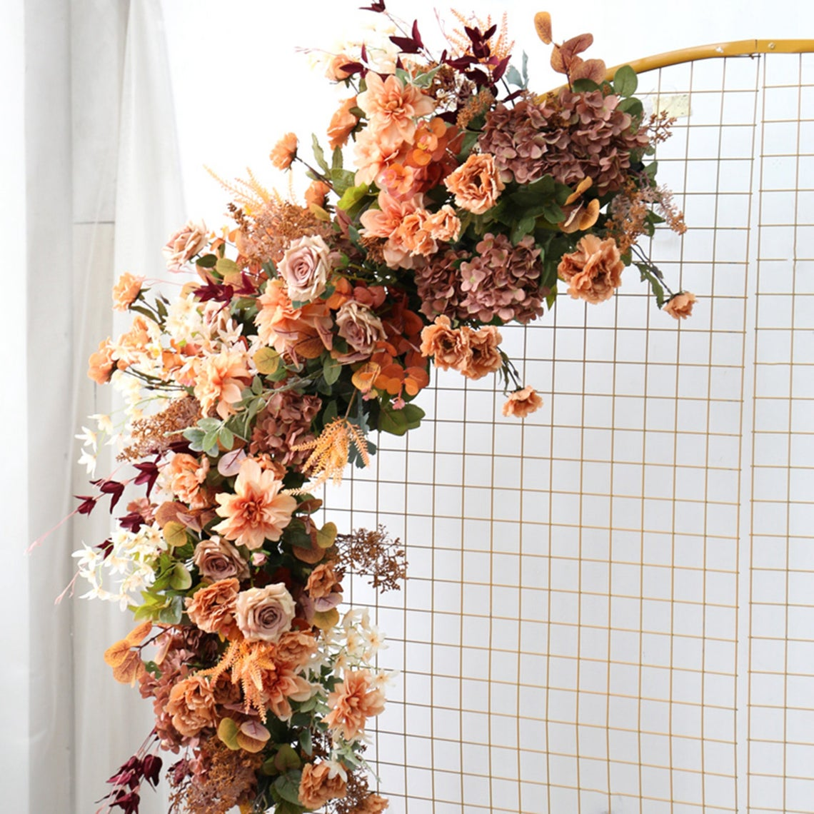 faux fall wedding flowers attached to a circular gridded stand