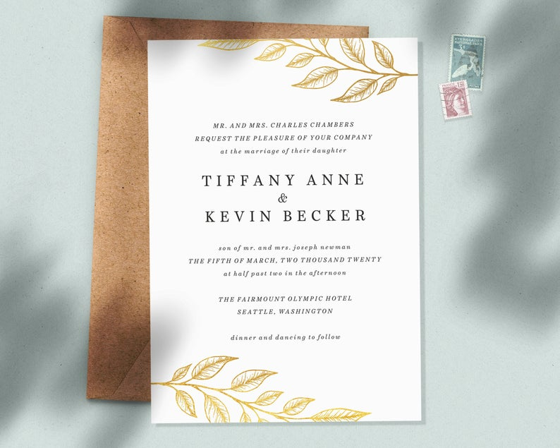 Flat lay image of traditional wedding invitation wording with gold leaf pattern