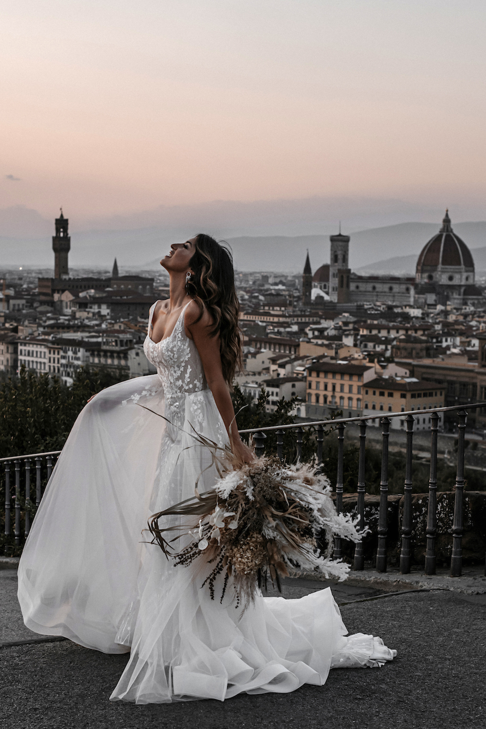 Woman standing in front of city scape, looking to sky, holding up the skirt of white wedding dress in one hand, dried flowers in the other